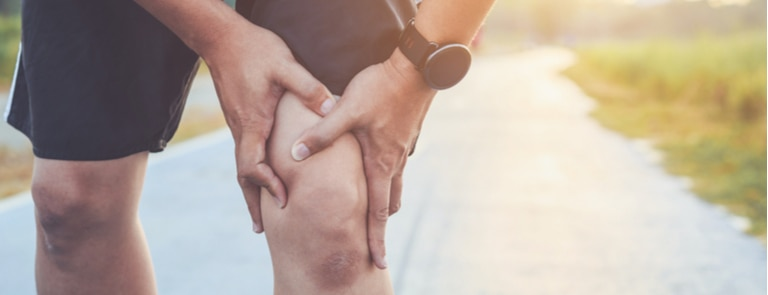 closeup of man holding knee in pain during run on road