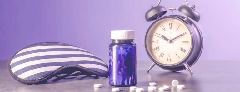 alarm clock next to sleeping mask and melatonin tablets