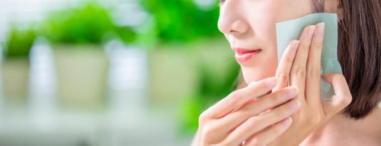 asian women dabbing blotting paper on oily skin