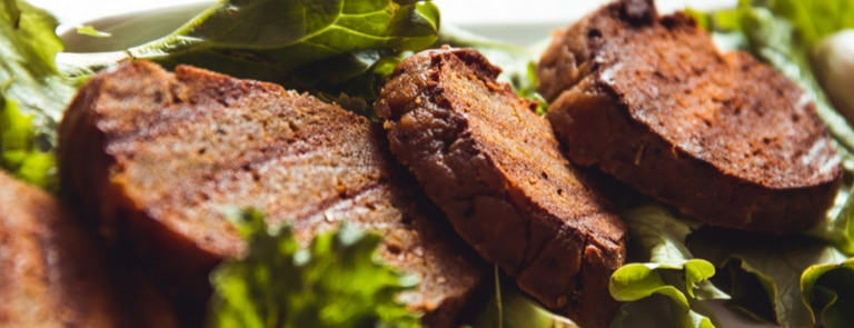 cooked seitan on a bed of lettuce