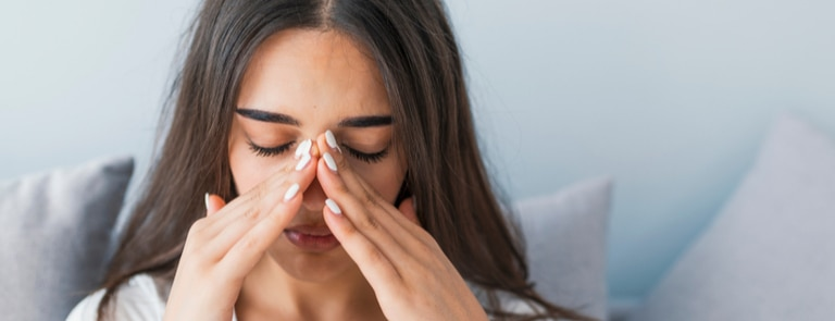 woman with fingers on sinuses uncomfortable