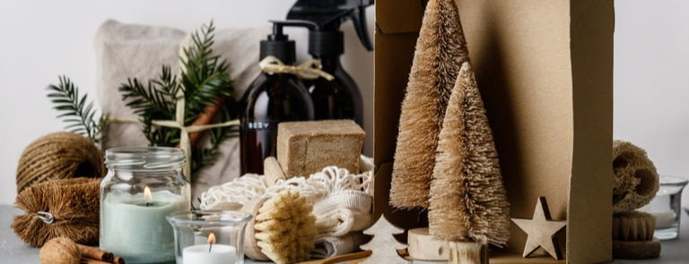 Christmas decorations made from sustainable materials surrounded by candles and sustainable beauty products such as brush and spray bottles.