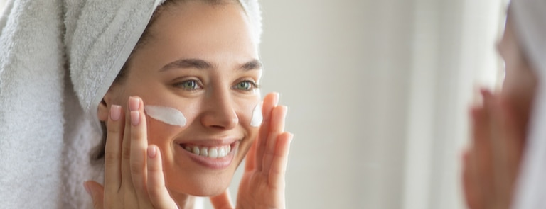 woman in hair towel applying face cream happily
