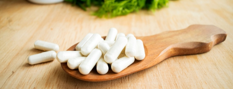 white vitamin K tablets on wooden spoon
