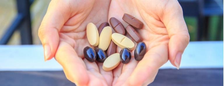 woman's hands holding multivitamins