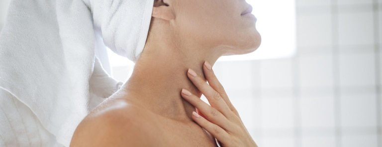 woman looking at neck in mirror