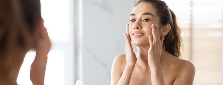 A smiling women applying facecream to her cheek