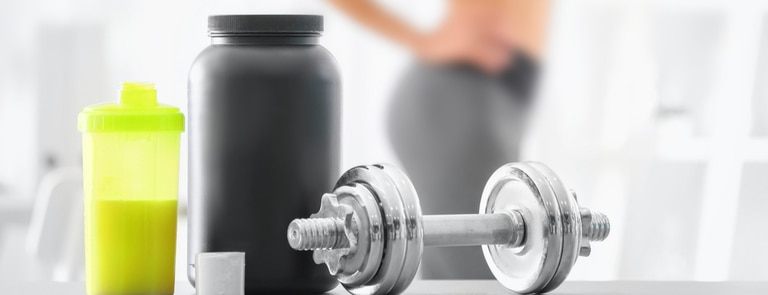 creatine sports supplement next to dumbell
