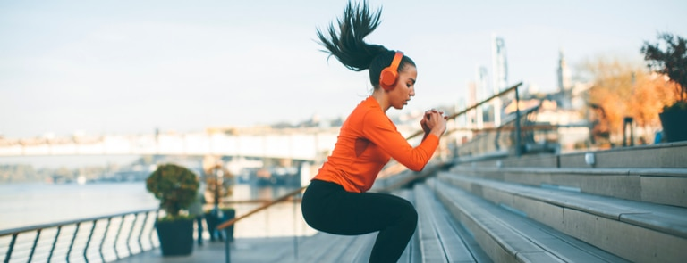 woman doing squat jumps on stairs outdoors