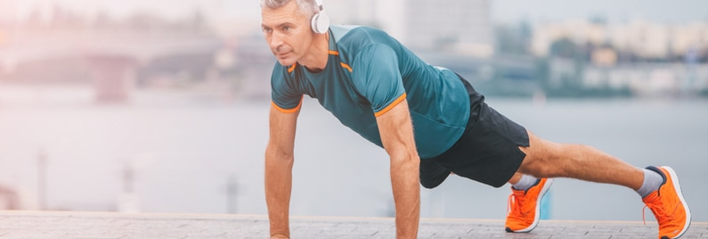 Fitness middle aged man doing push-ups on the riverside.
