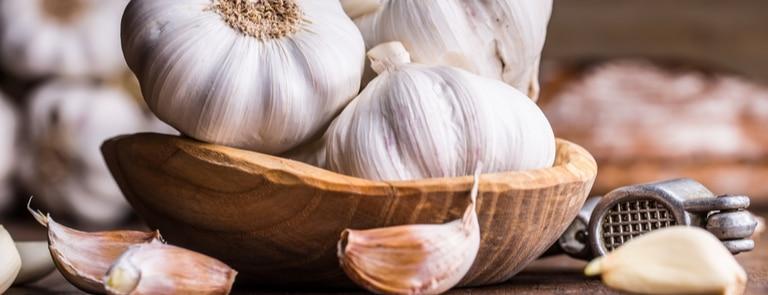 cloves of garlic with a garlic press