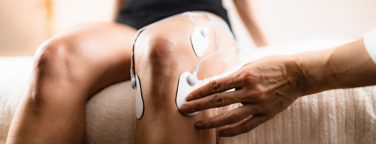 person applying a muscle stimulator to their knee