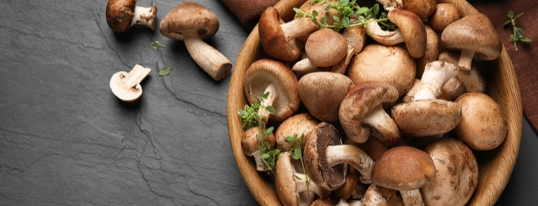 mushrooms in a wooden bowl on a granite surface