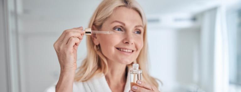 mature woman using hyaluronic acid serum on face