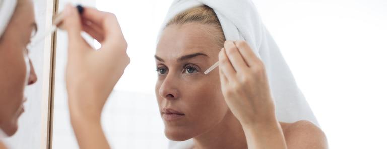 woman applying face serum in mirror