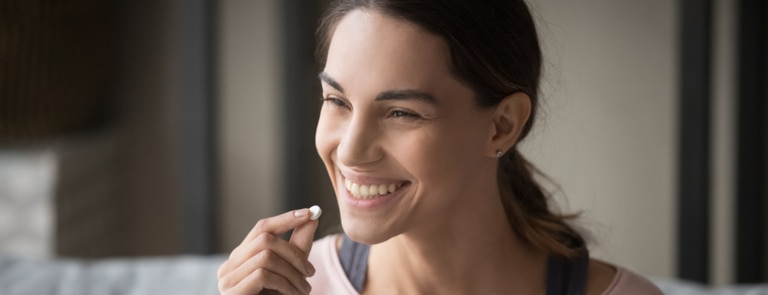 woman with healthy skin taking vitamin tablet