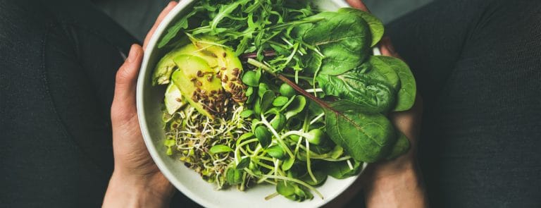 Bowl of green vegetables and seeds being held