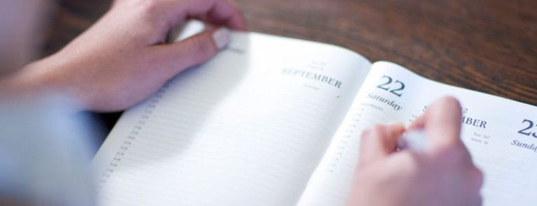 A Person writing in a Calendar