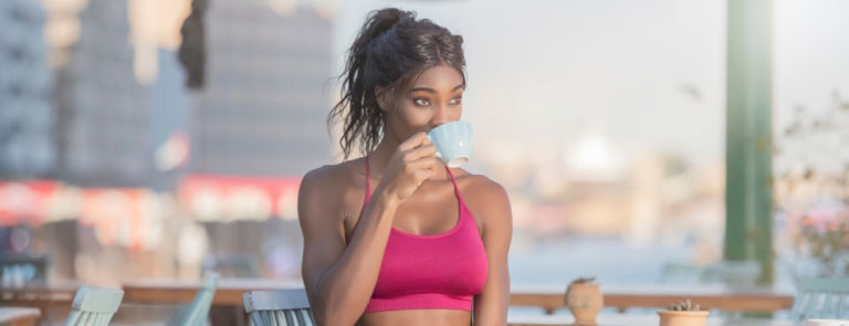 an african american women in workout clothes sitting at a cafe bench drinking coffee
