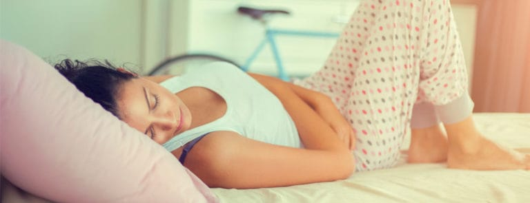 Women lying on bed, wearing pyjamas