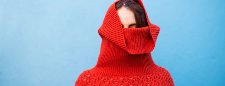 Woman with red turtle neck covering face