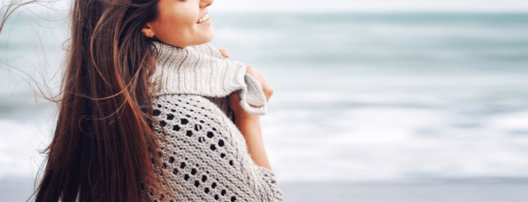 Woman smiling on beach wearing knitted jumper