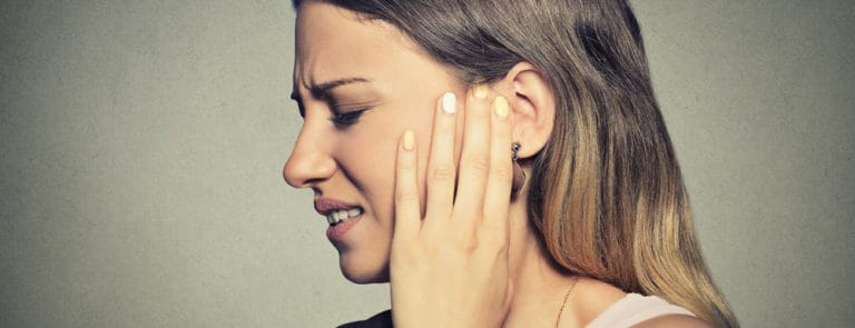 Woman looking uncomfortable with hand on ear