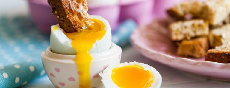 Toast in boiled egg with runny yolk in a heart-patterned egg cup