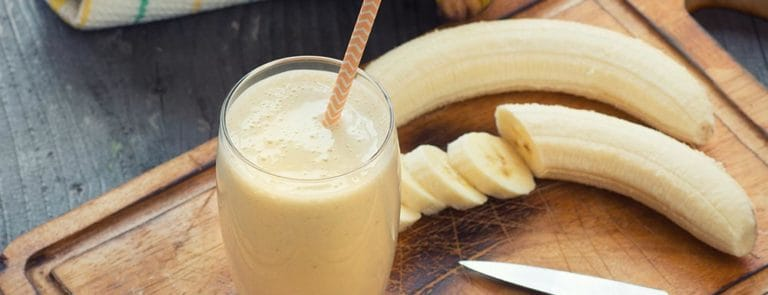 Banana smoothie with straw next to chopped up banana