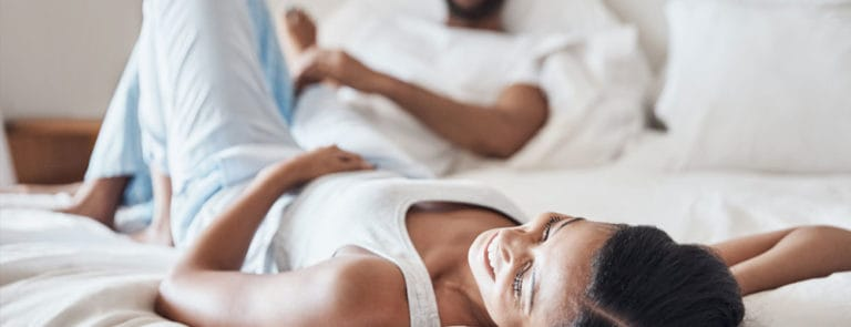 Couple sitting on a bed in pyjamas smiling