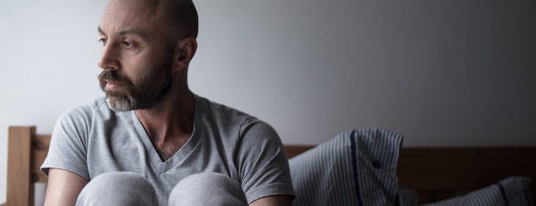 Bearded man sat on bed