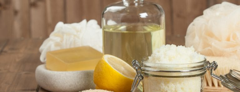 Lemon, sugar, coconut oil and scrub on wooden table