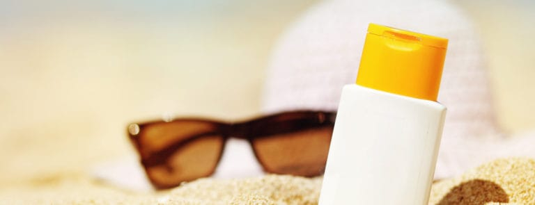 Sun lotion and sunglasses on sand