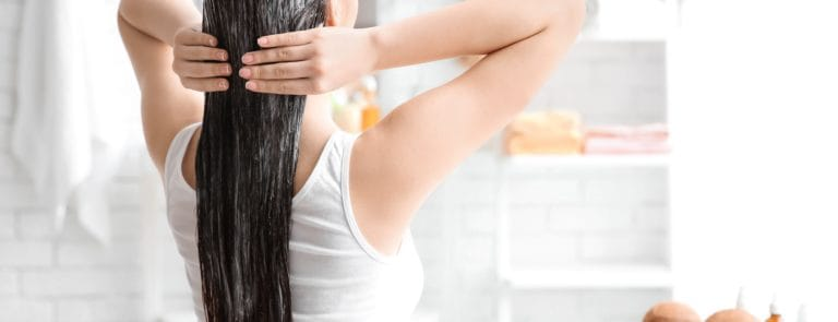 Young woman applying oil onto hair in bathroom