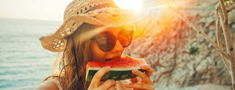 Young woman eating a large slice of watermelon on a beach