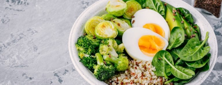 Boiled eggs, broccoli, spinace, brussels and quinoa in a white bowl