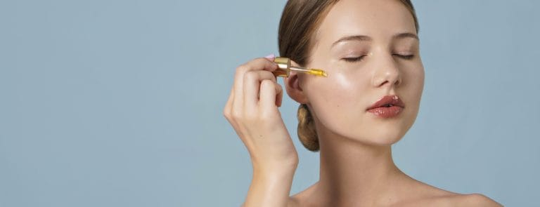 portrait of young woman applying serum on her face on blue background