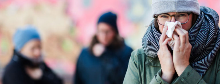 woman wearing a coat and scarf, using a tissue to wipe her nose