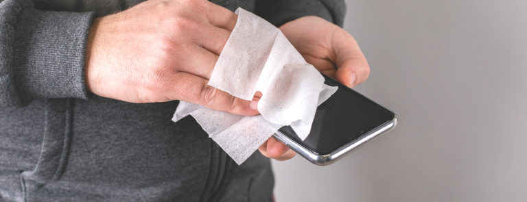 A men cleaning his phone with a wipe