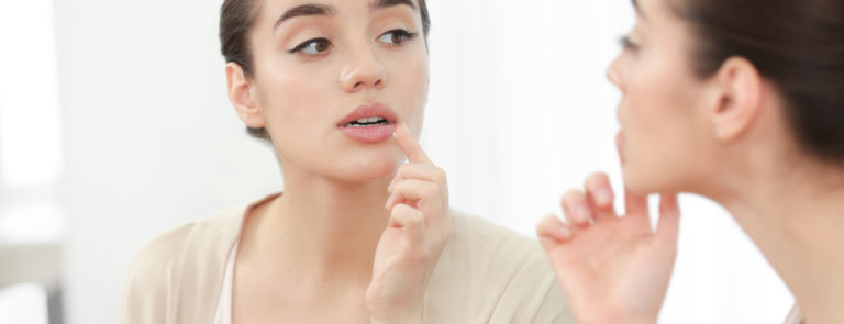 woman looking at her lip at a potential cold sore