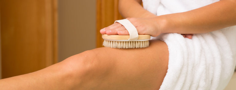 woman using body brush to get rid of cellulite