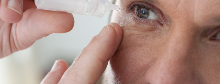 man using eye drops to get rid of his red eyes