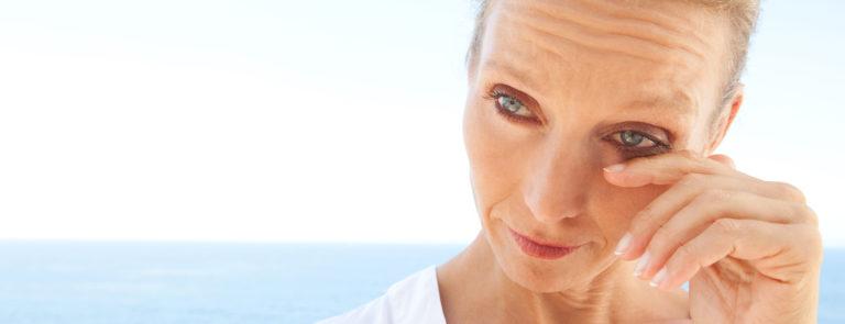 woman wiping her watering eye