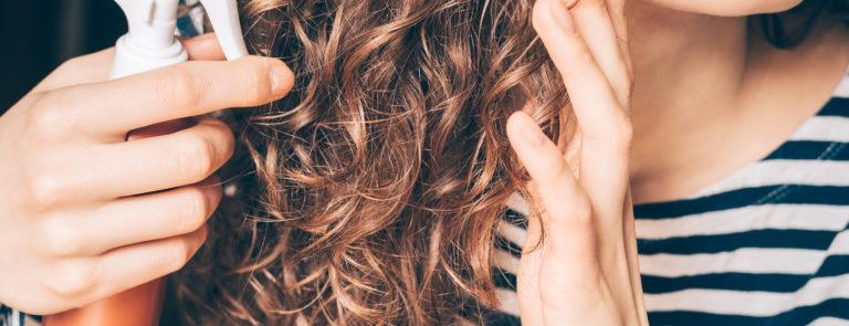 woman applying sea salt spray to curl her hair naturally