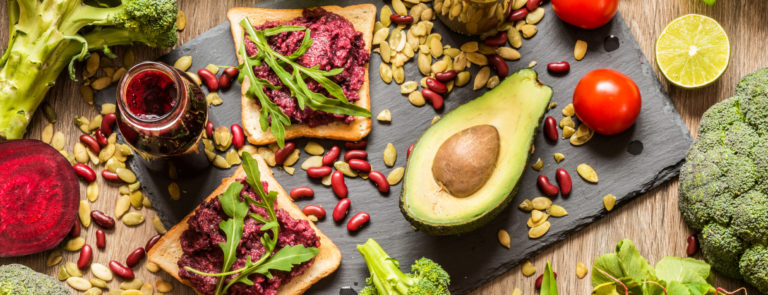 A variety of vegan foods, including beetroot jam on bread with asparagus, avocado's, tomatoes and lettuce.