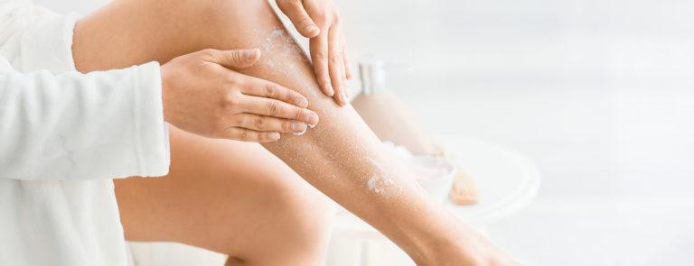 woman using a scrub on her legs