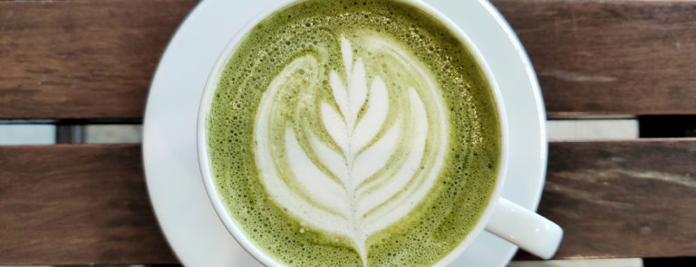Matcha drink in a mug with a latte art flower inside.