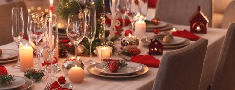 A dining table set up and ready for Christmas dinner. With red napkins, wine glasses and candles.