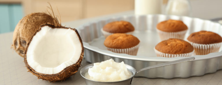 A tray full of cupcakes with a cocnut in front and a bowl of coconut oil with a spoon in. A bottle of milk behind the cupcakes.