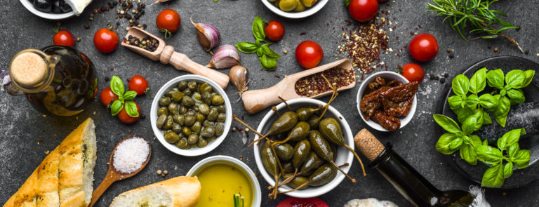 A spread of olives, bread, oils and an array of vegetables on a table.